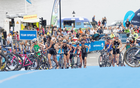 ciclos: STOCKHOLM - JUL 02, 2016: Group of triathletes running with cycles in the transition zone in the Womens ITU World Triathlon series event July 02, 2016 in Stockholm, Sweden Editorial