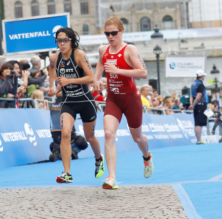 transition: STOCKHOLM - JUL 02, 2016: Takahashi and Annen fighting in the transition zone in the Womens ITU World Triathlon series event July 02, 2016 in Stockholm, Sweden Editorial