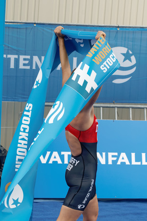 ber: STOCKHOLM - JUL 02, 2016: Winning triathlete Flora Duffy (BER) lifting the finishing tape at the finish in the Womens ITU World Triathlon series event July 02, 2016 in Stockholm, Sweden