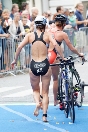 triathlete: STOCKHOLM - JUL 02, 2016: Triathlete Simone Ackermann running with cycle in the transition zone in the Womens ITU World Triathlon series event July 02, 2016 in Stockholm, Sweden