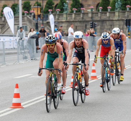 chased: STOCKHOLM, SWEDEN - JUL 02, 2016: Group of colorful male triathlete cyclists, Dan Wilson (AUS) chased by the Brownlee brothers (GBR) in the Mens ITU World Triathlon series event July 02, 2016 in Stockholm, Sweden