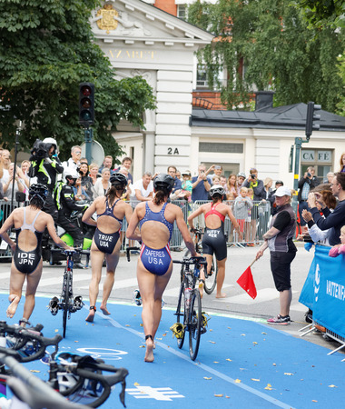 ide: STOCKHOLM - JUL 02, 2016: Triathletes running with cycle in the transition zone in the Womens ITU World Triathlon series event July 02, 2016 in Stockholm, Sweden