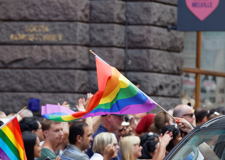 transexual: STOCKHOLM, SWEDEN - JUL 30, 2016: HPeople waiving the rainbow pride flag in the Pride parade July 30, 2016 in Stockholm, Sweden