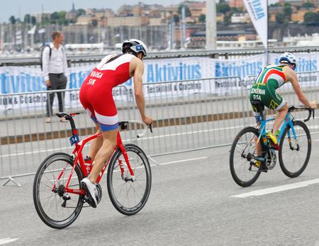 henri: STOCKHOLM, SWEDEN - JUL 02, 2016: Side view of two male triathlete cyclist Richard Varga (SVK), and Henri Schoeman (RSA) in the Mens ITU World Triathlon series event July 02, 2016 in Stockholm, Sweden