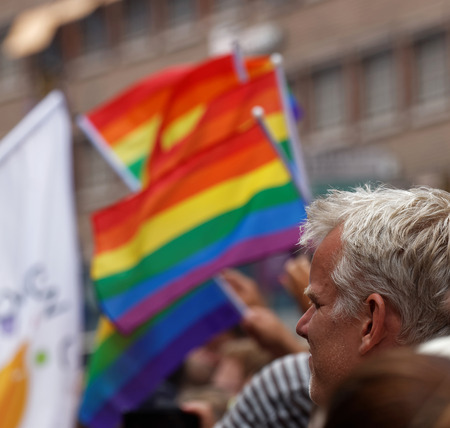 tolerancia: STOCKHOLM, SWEDEN - JUL 30, 2016: Man watching the waiving blurry rainbow pride flags in the Pride parade July 30, 2016 in Stockholm, Sweden Editorial