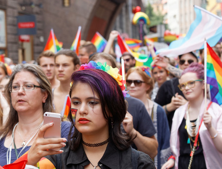 bisexual women: STOCKHOLM, SWEDEN - JUL 30, 2016: Girl in the Pride parade watching her phone in the Pride parade July 30, 2016 in Stockholm, Sweden Editorial
