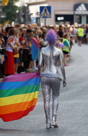 half naked: STOCKHOLM, SWEDEN - JUL 30, 2016: Half naked woman covered with silver body paint carrying the rainbow pride flag in the Pride parade July 30, 2016 in Stockholm, Sweden