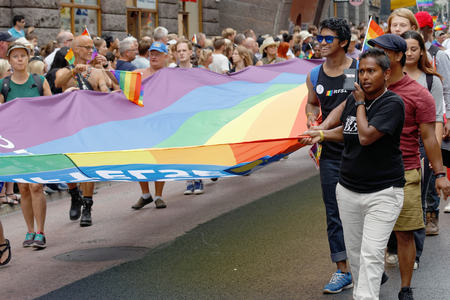 bisexual women: STOCKHOLM, SWEDEN - JUL 30, 2016: HGroup of people carrying a very large rainbow pride flag in the Pride parade July 30, 2016 in Stockholm, Sweden