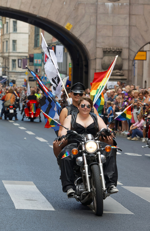 bisexual women: STOCKHOLM, SWEDEN - JUL 30, 2016: Two woman dressed in leather clothes on a motorcycle decorated with pride flags in the Pride parade July 30, 2016 in Stockholm, Sweden Editorial