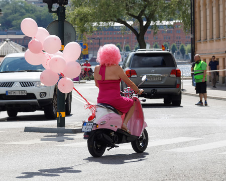 STOCKHOLM, SWEDEN - JUL 30, 2016: Woman dressed in pink color driving a pink motorcycle in the Pride parade July 30, 2016 in Stockholm, Sweden Editorial