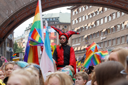 tall man: STOCKHOLM, SWEDEN - JUL 30, 2016: Roughed, tall man dressed in red and black with a funny hat in the Pride parade July 30, 2016 in Stockholm, Sweden