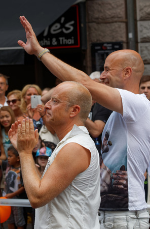 comedian: STOCKHOLM, SWEDEN - JUL 30, 2016: The swedish writer and comedian Jonas Gardell and his man Mark Levengood clapping hands in the Pride parade July 30, 2016 in Stockholm, Sweden