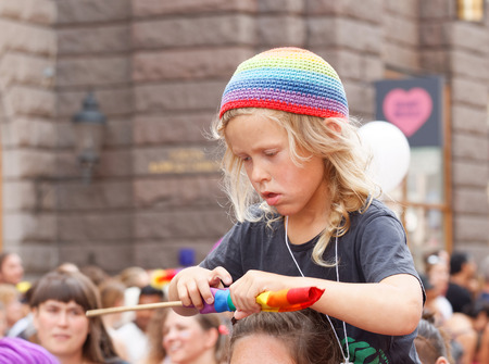 STOCKHOLM, SWEDEN - JUL 30, 2016: Blonde little boy wearing a rainbow hat, fixing the rainbow flag sitting on his mothers shoulders in the Pride parade July 30, 2016 in Stockholm, Sweden Editorial