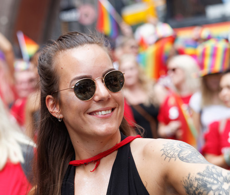 STOCKHOLM, SWEDEN - JUL 30, 2016: Young smiling girl wearing sunglasses and tatoo in the Pride parade July 30, 2016 in Stockholm, Sweden