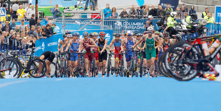 STOCKHOLM - JUL 02, 2016: Large group of running triathletes running with bicyles in the transition zone in the Mens ITU World Triathlon series event July 02, 2016 in Stockholm, Sweden Redakční