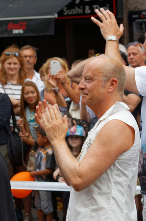 comedian: STOCKHOLM, SWEDEN - JUL 30, 2016: The swedish writer, comedian and performer Jonas Gardell clapping hands in the Pride parade July 30, 2016 in Stockholm, Sweden