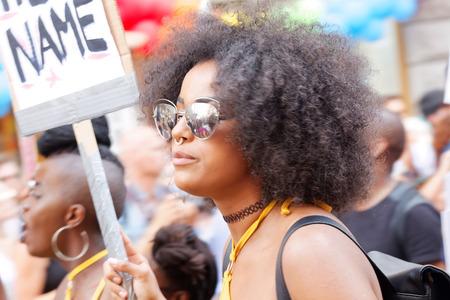 transexual: Estocolmo, Suecia - 30 de julio, 2016: Mujer con el pelo afro y gafas de sol que llevan a cabo una muestra en el desfile del orgullo 30 de de julio de, 2016, Estocolmo, Suecia Editorial