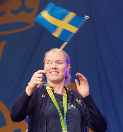 STOCKHOLM, SWEDEN - AUG 21, 2016: Swedish female soccer keeper Hedvig Lindahl waiving the swedish flag when the swedish olympic athletes are celebrated in Kungstradgarden, Stockholm,Sweden,August 21,2016