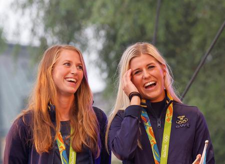 bandera de suecia: Estocolmo, Suecia AUG - 21 de, 2016: Feliz sueco equipo de fútbol femenino cuando los atletas olímpicos suecos se celebran en Kungstradgarden, Estocolmo, Suecia, Agosto 21,2016