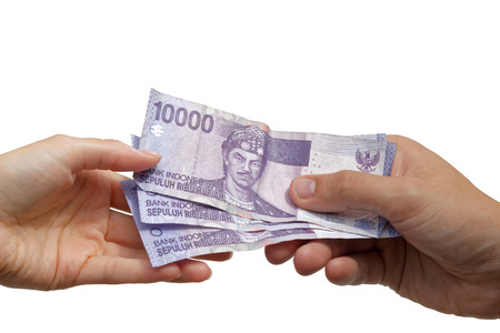 rupiah: Paying - hand giving Indonesian rupiah banknotes to another hand