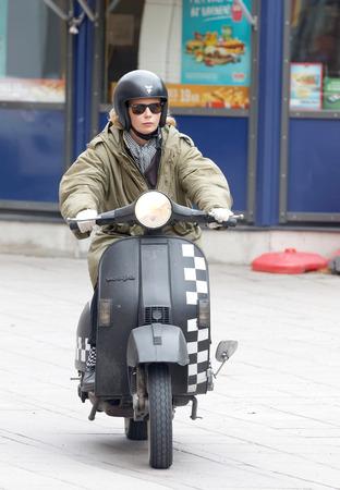 Estocolmo, Suecia - 03 de septiembre, 2016: Mods mujer que conducía un negro retro scooter Vespa en caso Mods vs ejes de balancín en el puente de Saint Eriks, Estocolmo, Suecia, 03 de septiembre, el año 2016