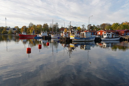 windless: Small fishing boats in the harbor reflecting in the water a perfect sunny, windless morning in October 02, 2016 in Grisslehamn, Stockholm, Sweden