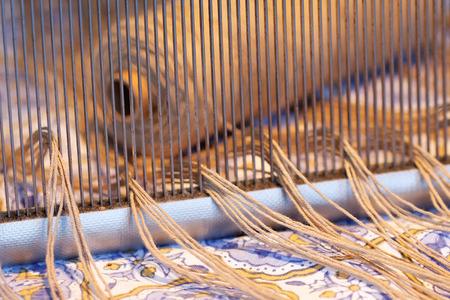 WEAVER: Preparing a loom before starting to make carpets. Warm light.