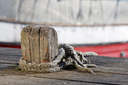 Wooden bollard, rope and fishing boats in the background