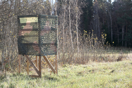 moose hunting: Hunting tower inrended for moose hunting with camouflage net on the meadow Stock Photo