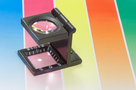 Magnifier or printers loupe sits on a colorful CMYC test sheet in a pre-press workshop Stock Photo