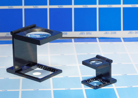 mottle: Two magnifier or printers loupe sits on a cyan test sheet in a pre-press workshop