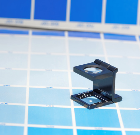mottle: Magnifier or printers loupe sits on a cyan test sheet in a pre-press workshop