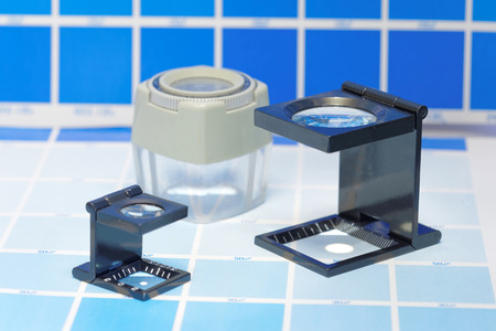 mottle: Three magnifier or printers loupe sits on a cyan test sheet in a pre-press workshop Stock Photo