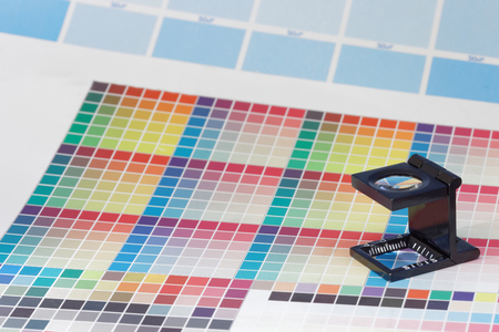 mottle: Magnifier or printers loupe sits on a colorful CMYK test sheet in a pre-press workshop
