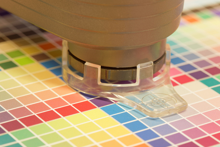 Closeup of spectrometer used for proofing on a leaf of the multi color test print in a pre-press workshop