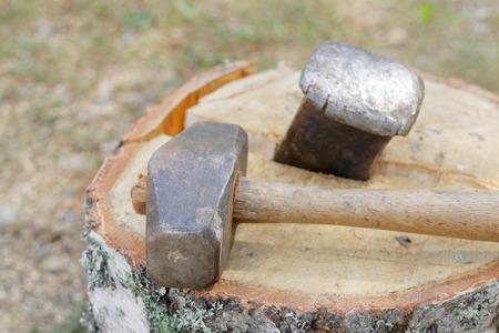 Sledgehammer and a wedge splitting a birch log Standard-Bild