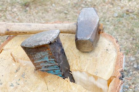 Sledgehammer and a wedge splitting a birch log Stock Photo