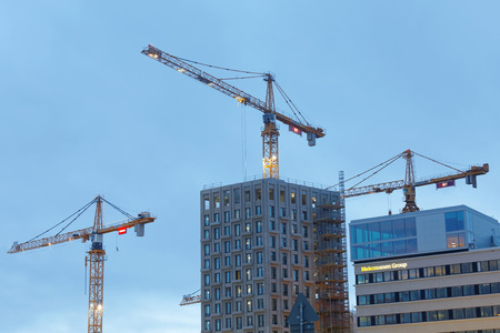 sihouette: STOCKHOLM - JAN 15, 2017: Sihouette of yellow cranes, blue sky and high buildings. January 15, 2017 in Hagastaden, Stockholm, Sweden Editorial