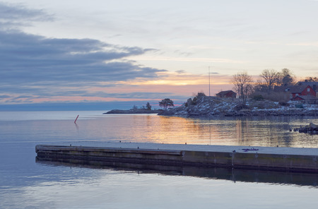Bridge in the sea at sunrise and distant red cottages Stock Photo