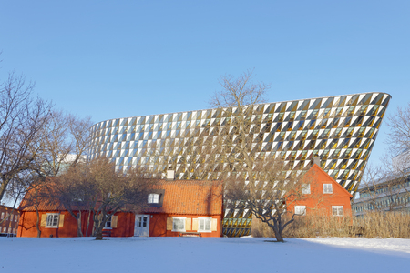 STOCKHOLM - JAN 15, 2017: The spectacular conference building Aula Medica at university hospital Karolinska institutet. Old red cottages and snow in the foreground. January 15, 2017 in Stockholm, Sweden