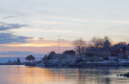 Rural red cottages in the archipelago at sunrise