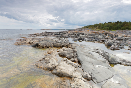 Dramatic, threatening rocky coastline, dark clouds and sea in the swedish archipelago