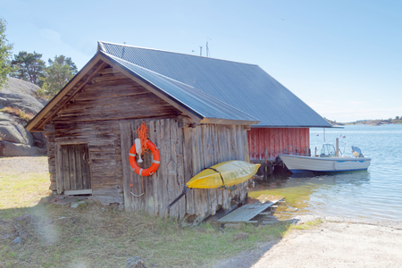 Very old aged gray boathouse, a boat and a canoe in the archipelago in Aaland, Finland