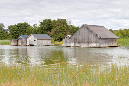 Gray decayed boathouses sea and weed in the archipelago in Aaland, Finland