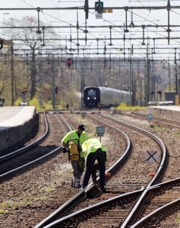 HASSLEHOLM, スウェーデン - 2016 年 5 月 5 日: 保線作業員、列車が駅に到着した時に鉄道を操作します。2016 年 5 月 5 日、Hassleholm、スウェーデン