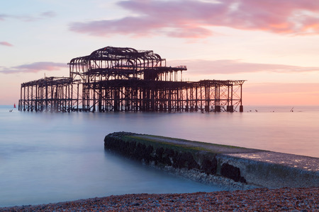 brighton: Abandoned West pier in Brighton at sunset, warm red colors. Soft water and pebbles in the foreground Stock Photo