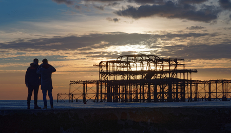 BRIGHTON, GREAT BRITAIN - FEB 24, 2017: Brighton west pier in warm evening light, silhouette of two people watching the construction. Pebbles in the foreground. February 24, 2017 in Brighton, Great Britain