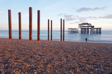 Iron skeleton of the abandoned West pier in Brighton at sunset, warm red colors. Pebbles in the foreground and silhouette of a man watching the construction