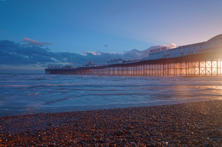 brighton: Brighton pier at sunset, warm red and blue colors. Pebbles in the foreground