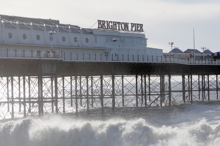 Stormy weather at the Brighton pier. Water splashing when meeting the pebbles